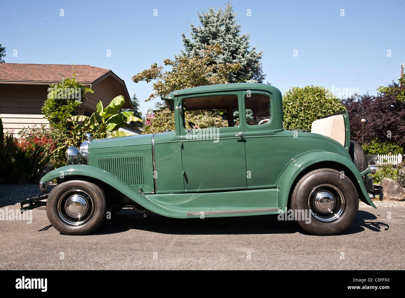 restored classic 1930 green Model A Ford car with open rumble seat parked in context of suburban driveway Edmonds Stock Photo