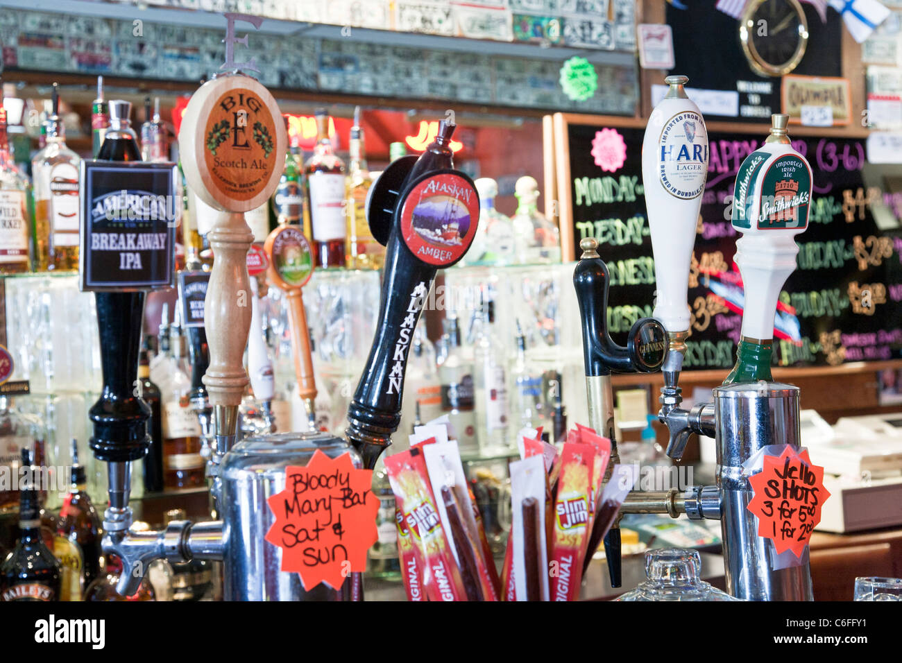 spigot handles with distinctive brand labels for various beers on tap in cheerful tavern Edmonds Washington - Stock Image