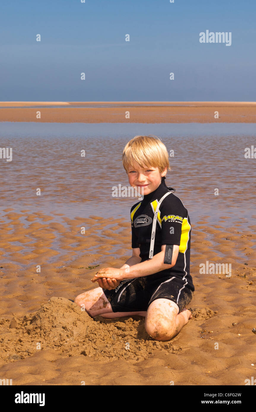 A seven year old boy playing on the beach in the sand wearing a wetsuit at Wells-next-the-sea , Norfolk , England - Stock Image