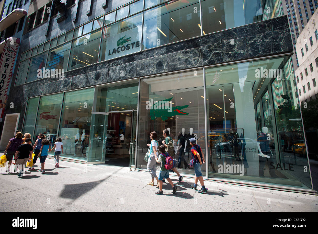 cbdb23a655e Hordes of shoppers pass the newly reopened Lacoste store on Fifth Avenue in  Midtown Manhattan in