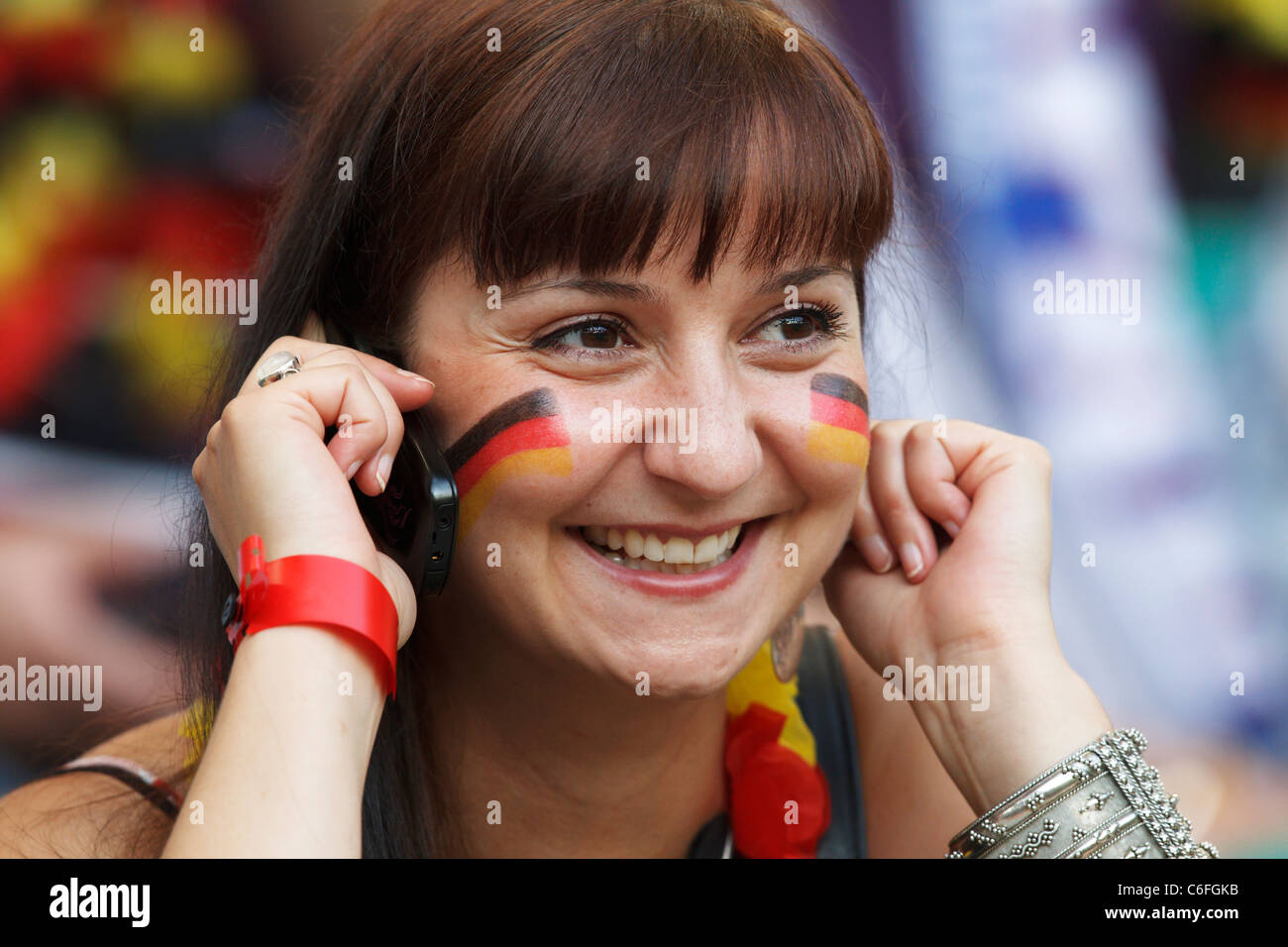 Germany supporter smiles while talking on her mobile phone at a 2011 Women's World Cup quarterfinal match between - Stock Image