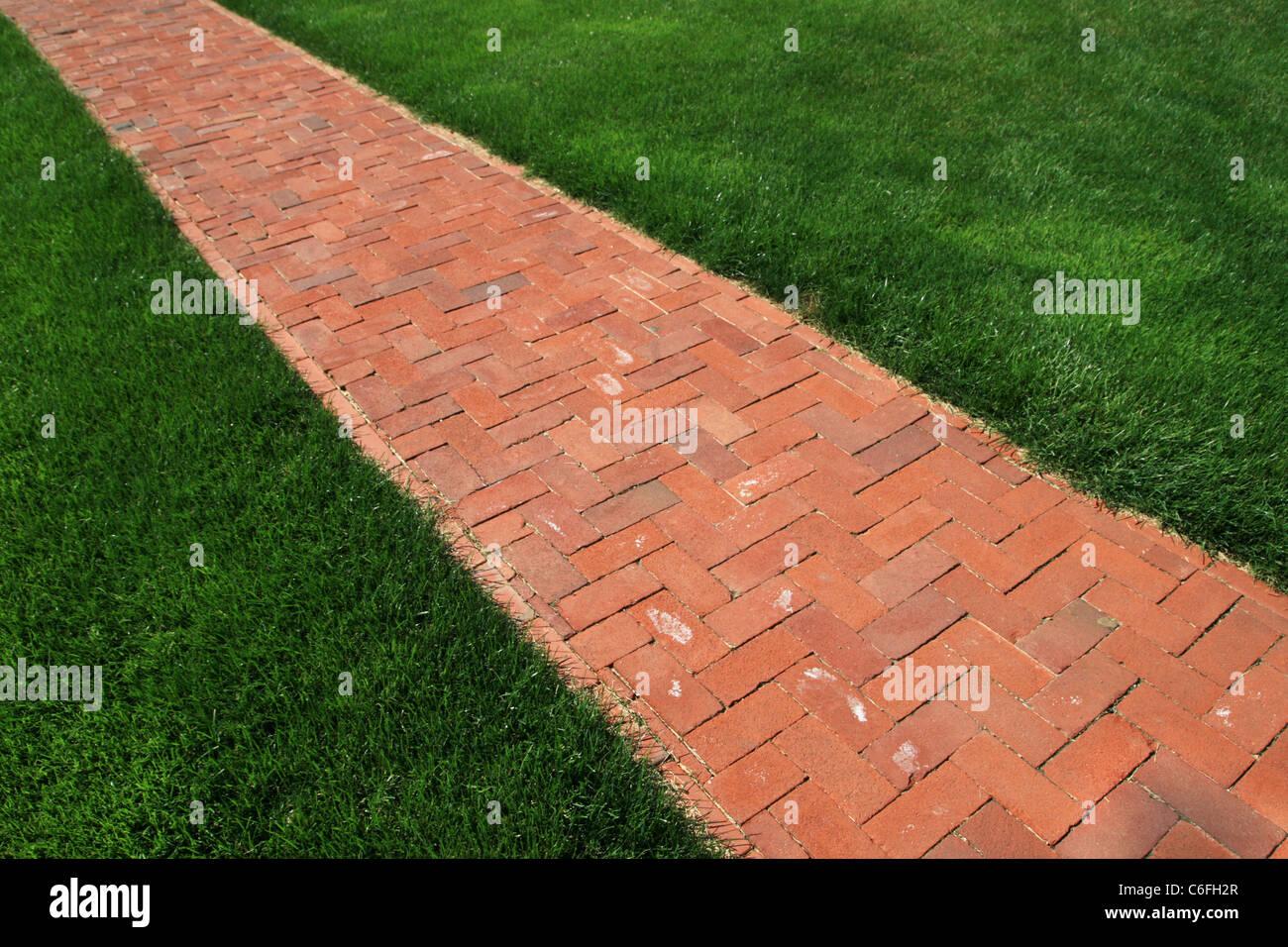 brick walkway diagonals across a green lawn - Stock Image