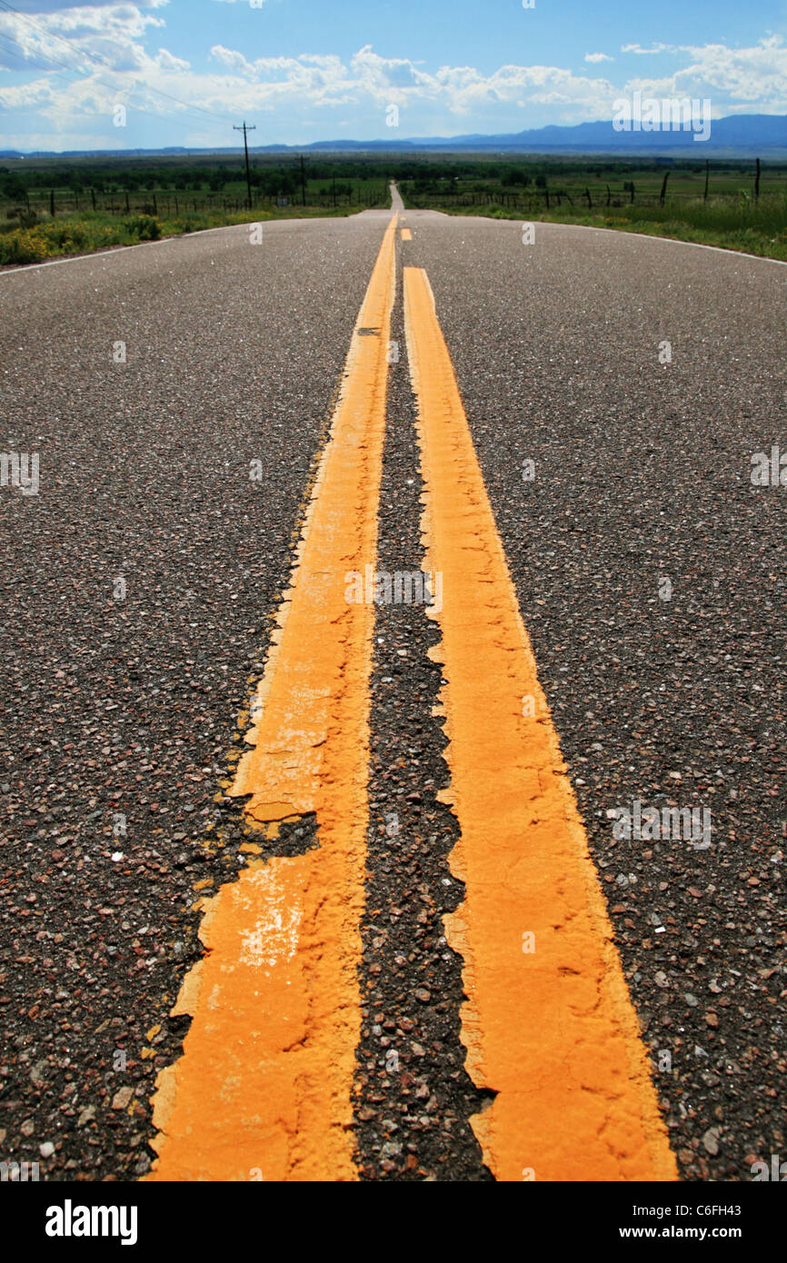 yellow lines on a rural road heading into the distance - Stock Image