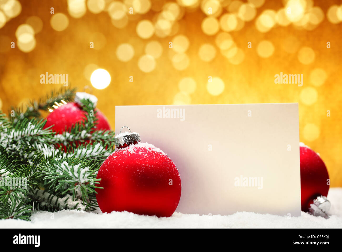 Closeup of Christmas balls,blank card and pine branch on festive background. - Stock Image
