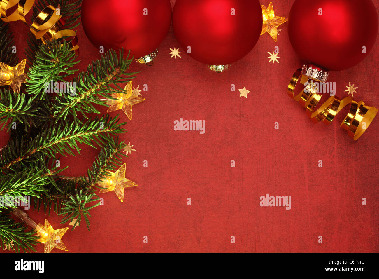 Christmas ornaments and electric lights on grunge background - Stock Image