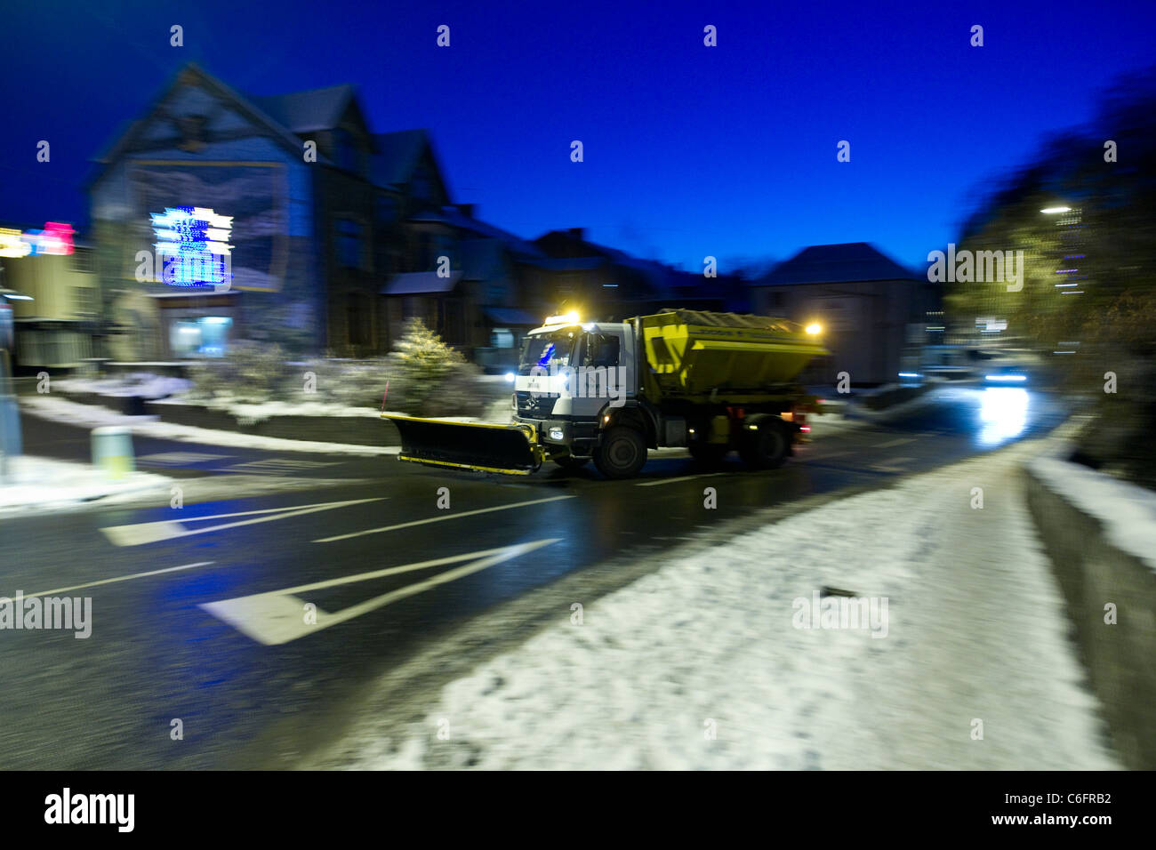 A snow plough gritter from Powys county council grits the roads around the centre of Builth Wells. - Stock Image