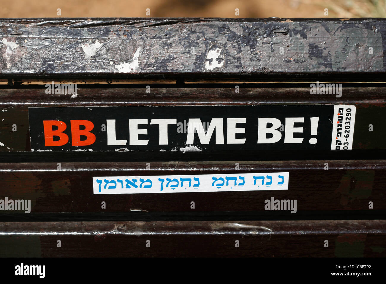 A sticker against the prime minister Benjamin Netanyahu fixed on a park bench seen in the Rothschild Boulevard in - Stock Image