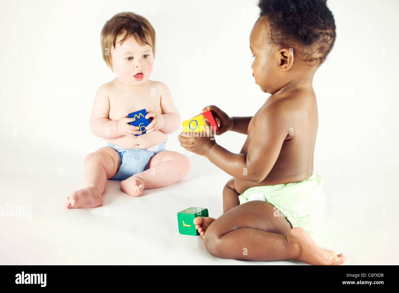 Two baby girls playing with alphabet bricks - Stock Image