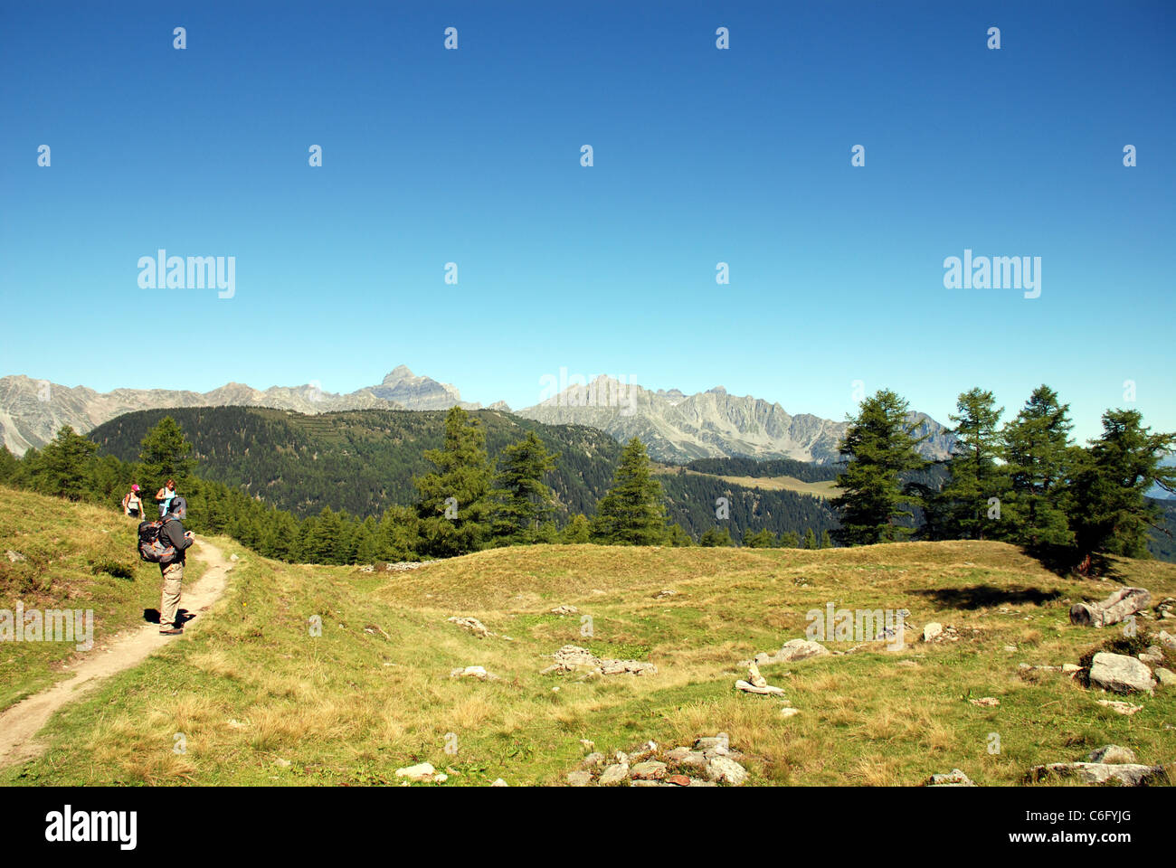 walkers follow a small path in the alps of France with high mountains in the background - Stock Image