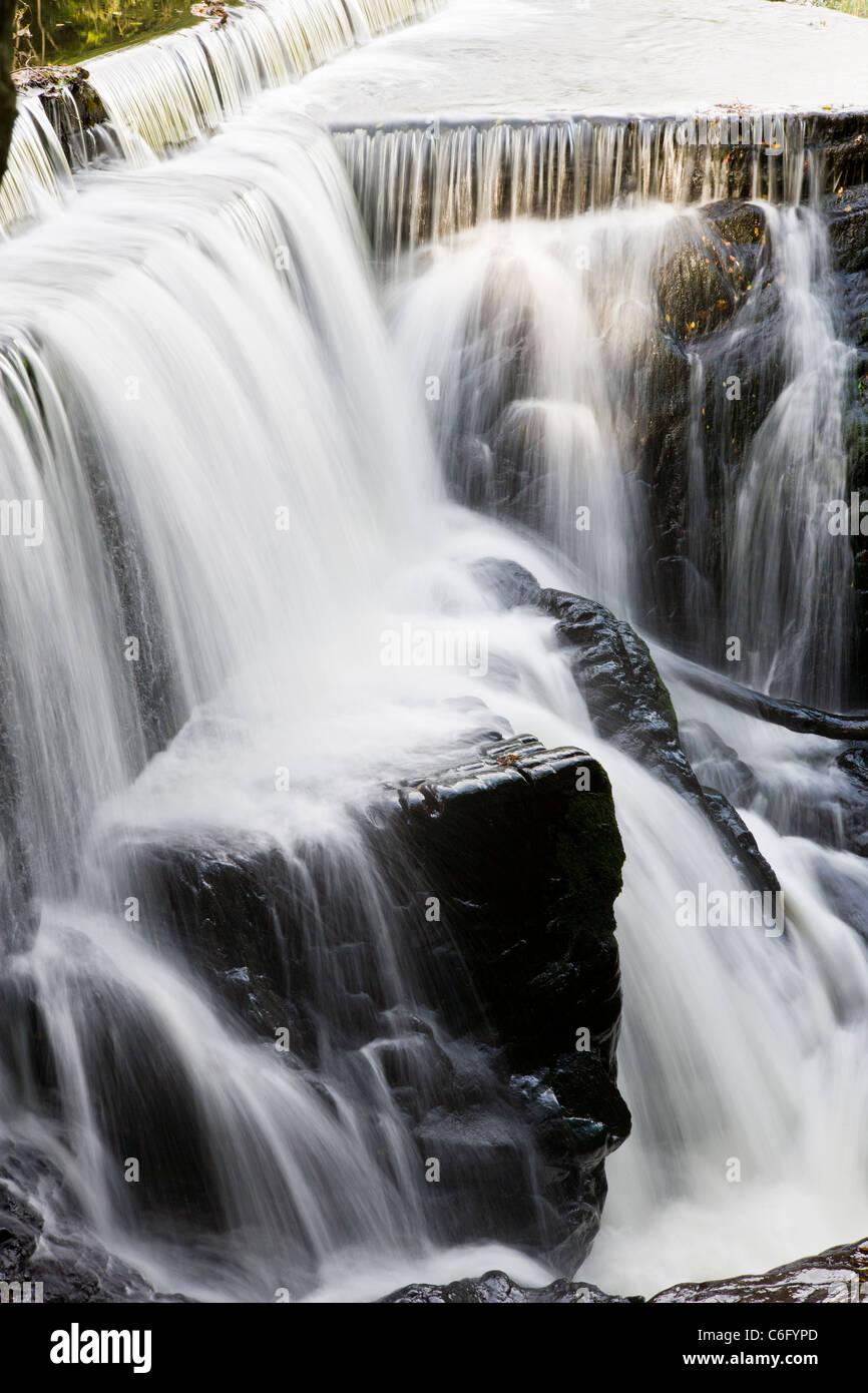 Long exposure - water splashing from rocks in a waterfall - Stock Image