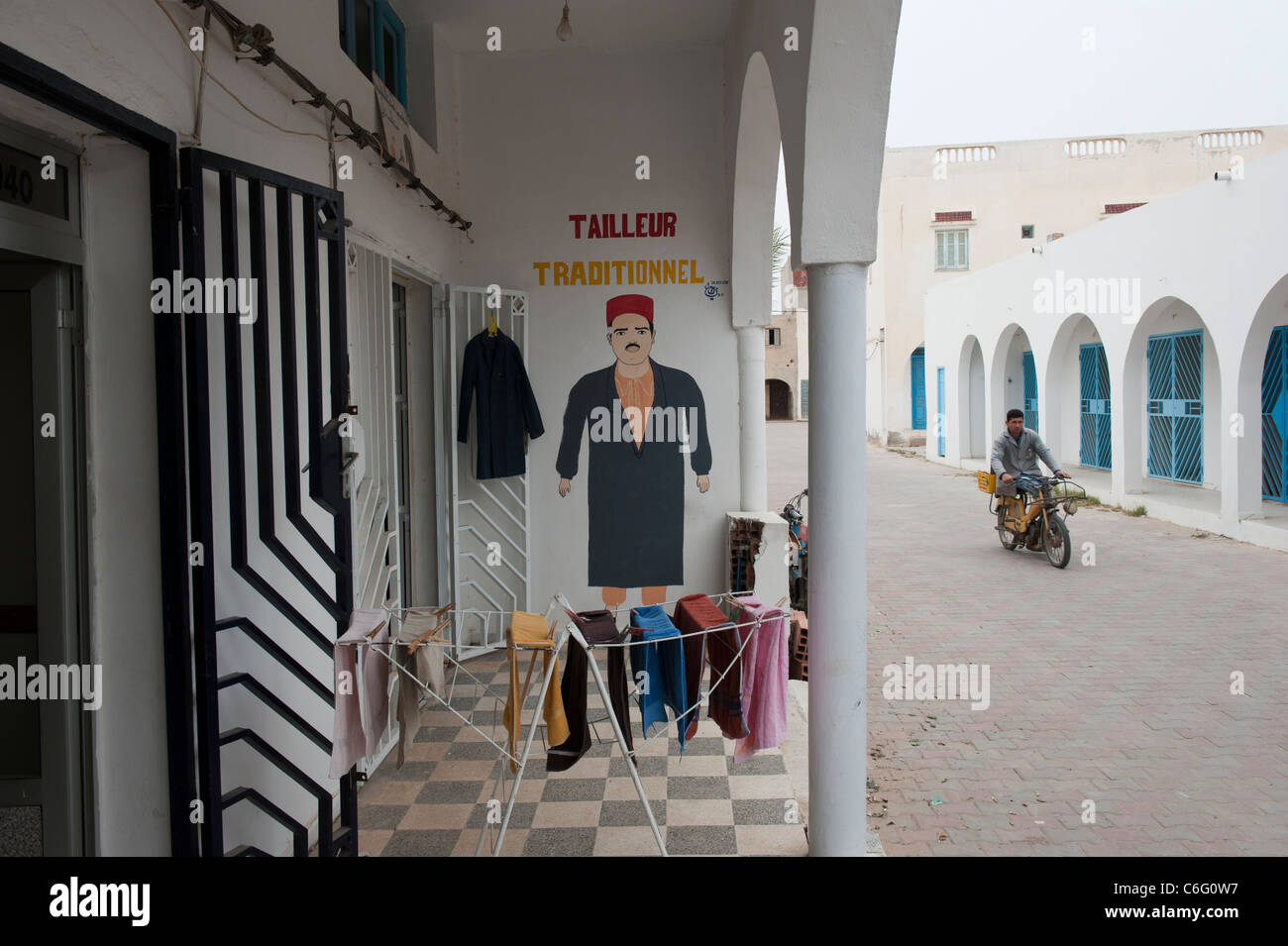 A Tunisian on a small motorbike passes a traditional tailors shop. Guellala. Djerba. Tunisia. North Africa - Stock Image