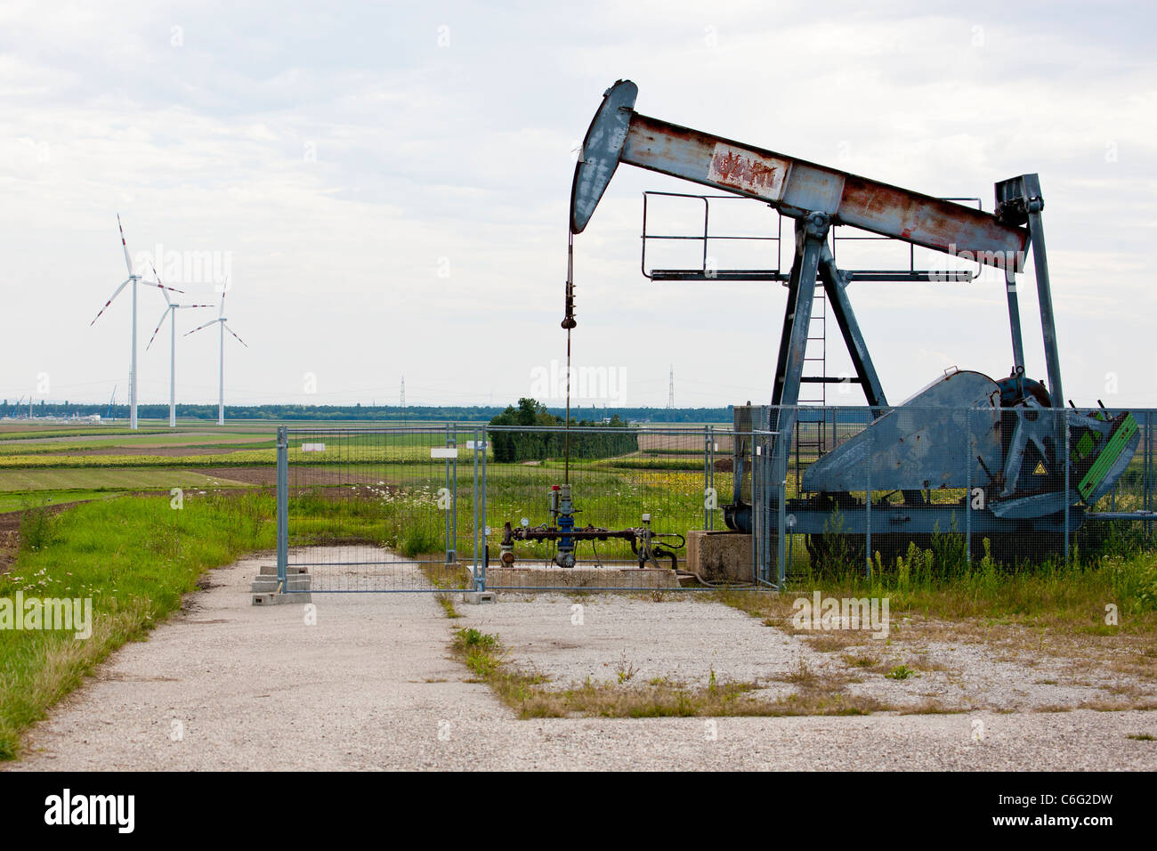 Crude oil pump with wind turbines in the background. - Stock Image