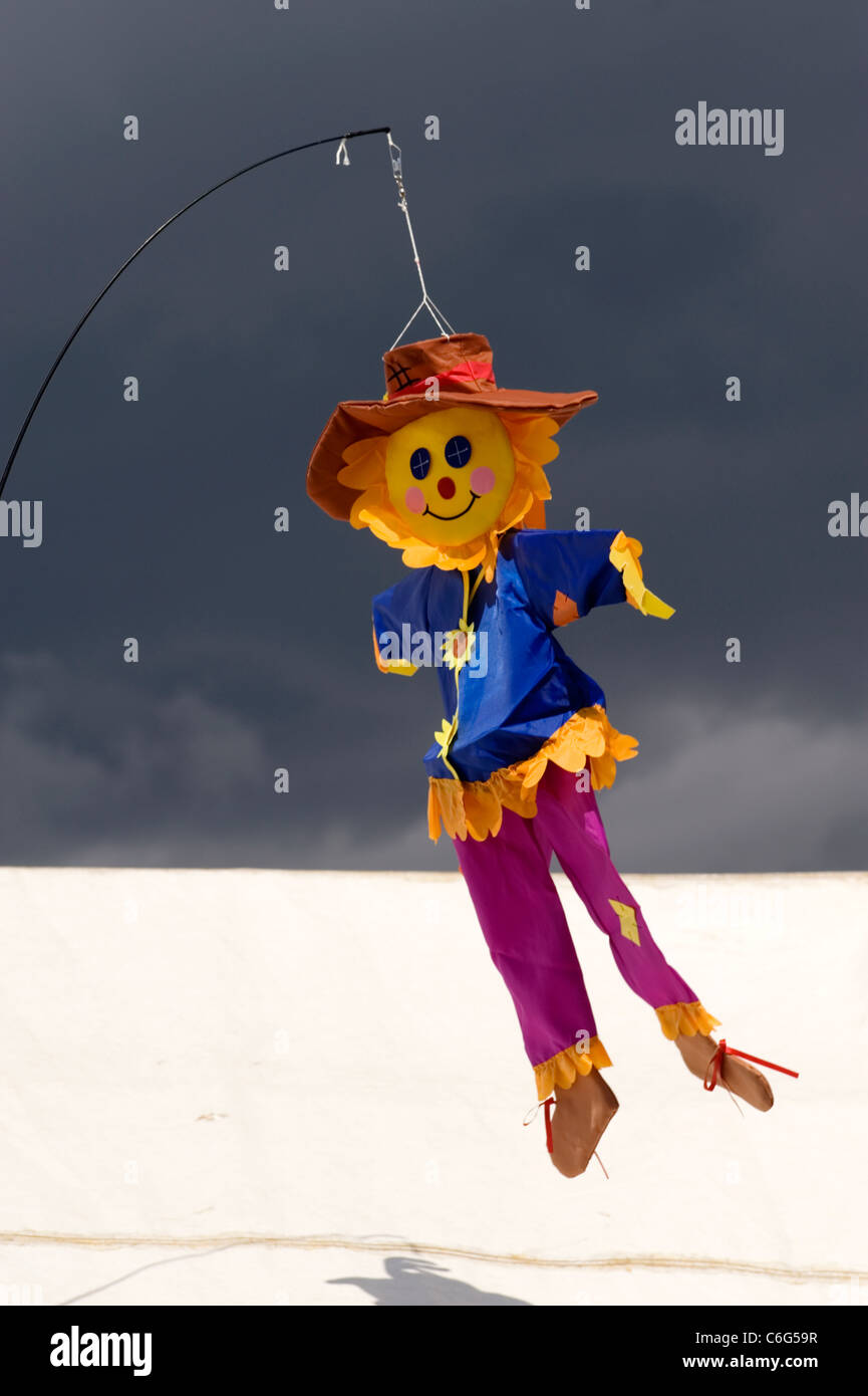 small colourful scarecrow kite flying in the breeze at southsea kite festival Stock Photo