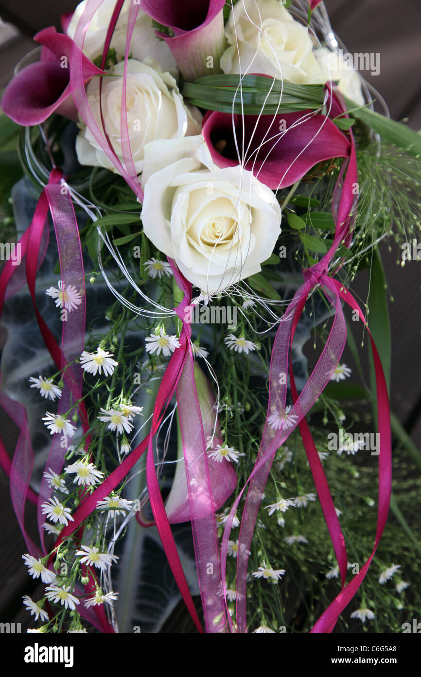 White roses and purple Callas decorated with beautiful, matching loops - upright format - Stock Image