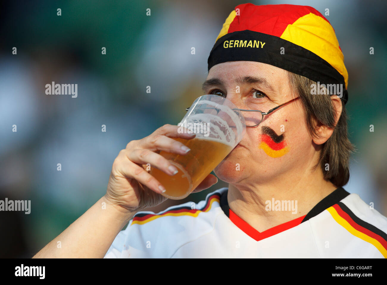 A Germany supporter drinks a glass of beer at a 2011 Women's World Cup quarterfinal soccer match between Germany - Stock Image