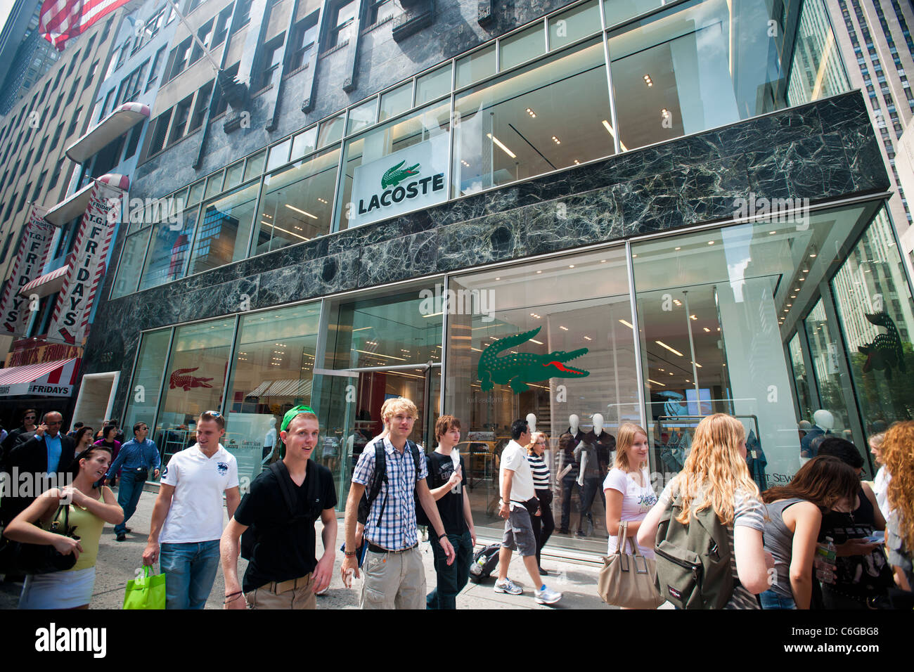 7ecef4f9721 Hordes of shoppers pass the newly reopened Lacoste store on Fifth Avenue in  Midtown Manhattan in