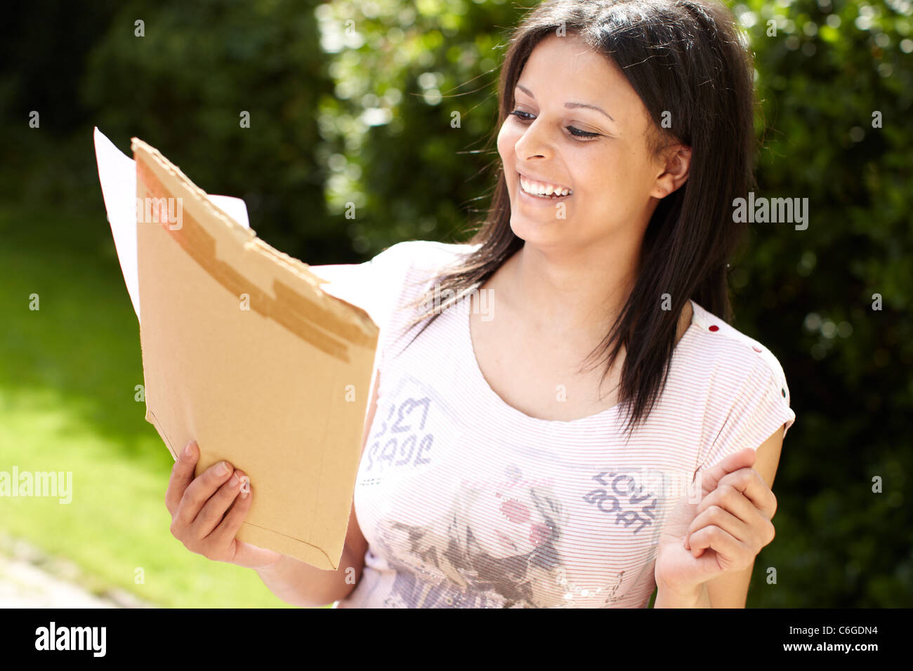 Ethnic girl sat with exam results - Stock Image