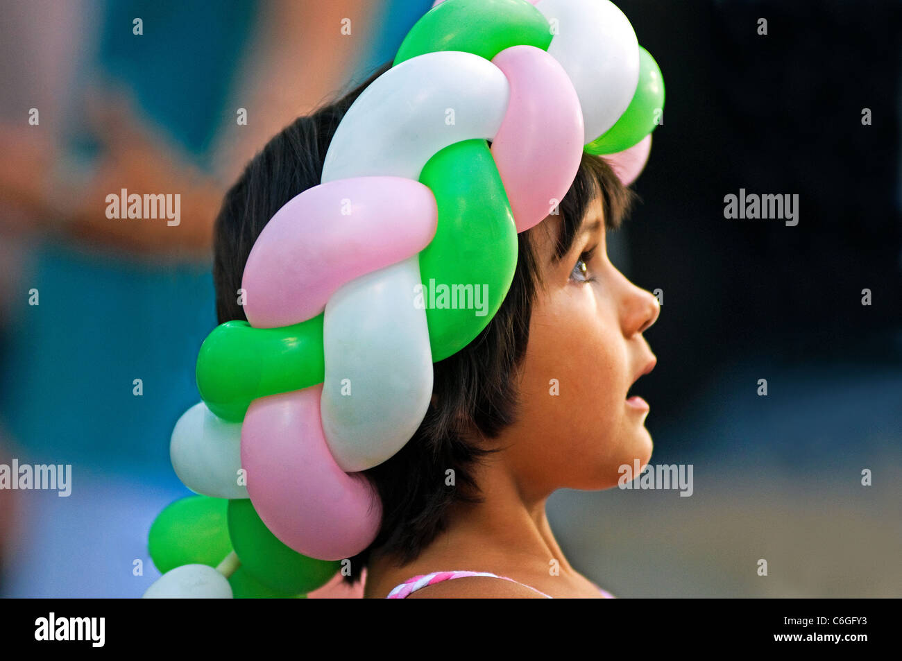 small girl female balloon people hat hats - Stock Image
