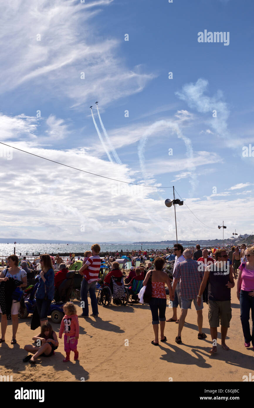 Bournemouth Air Festival visitors at Boscombe on promenade with 2 stunt planes performing in blue sky with wispy - Stock Image