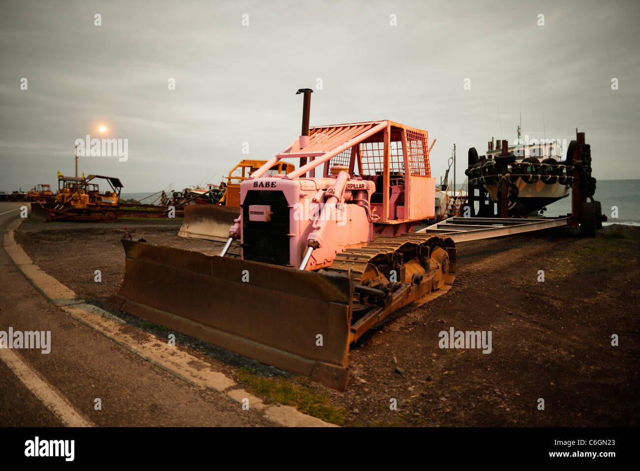 Bulldozer with fishing boat on trailer. An exposed beach at Ngawi, New Zealand, where boats are pulled out of the - Stock Image