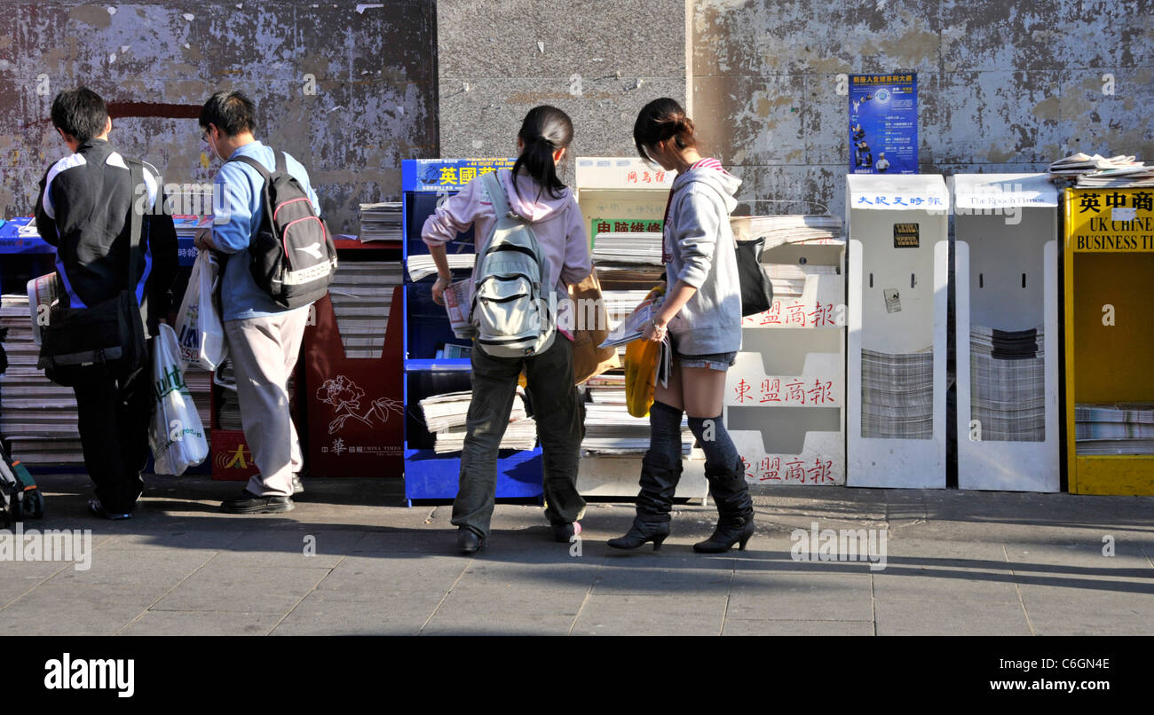 London china town street scene people helping themselves to free Chinese newspaper in Chinatown Gerrard Street London - Stock Image