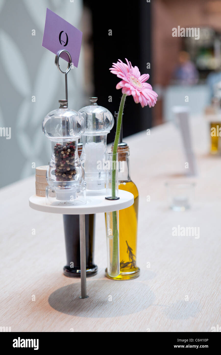 SALT AND PEPPER WITH GERBERA ON THE TABLE AT HOLYFIELDS, UNTEN DEN LINDEN, BERLIN, GERMANY - Stock Image