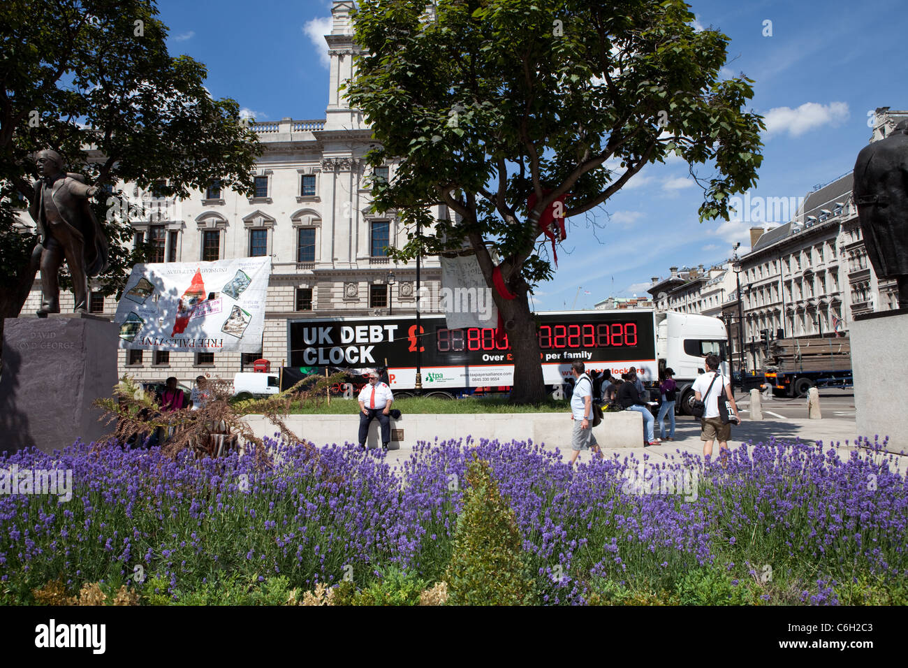 A van with 'UK Debt Clock' written on the side drives around Parliament Square as part of a protest during - Stock Image