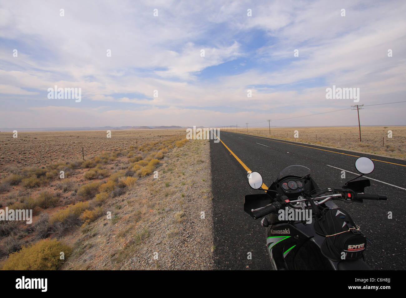 Scenic landscape with tar road and motorcycle - Stock Image