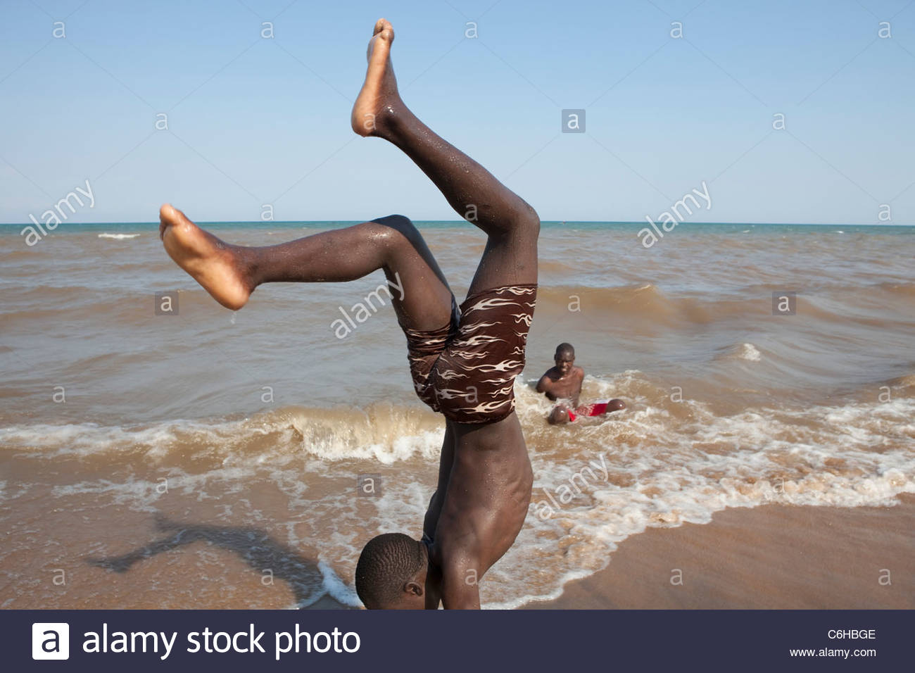 Local youths playing and doing handstands in the surf on the shore of Lake Malawi - Stock Image