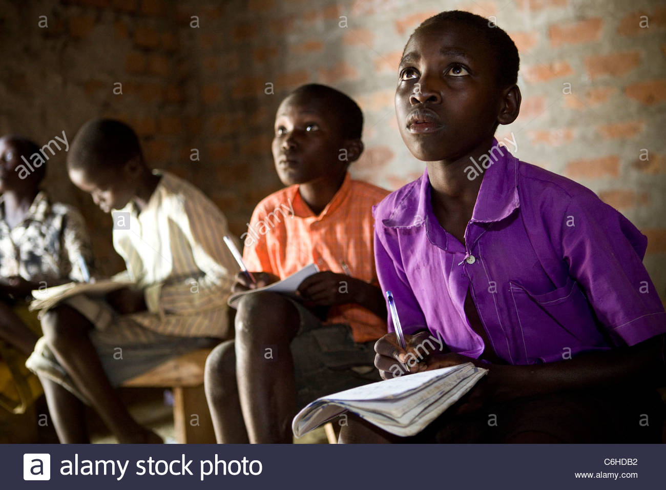 Primary school children writing into notebooks on their laps in a bare classroom - Stock Image