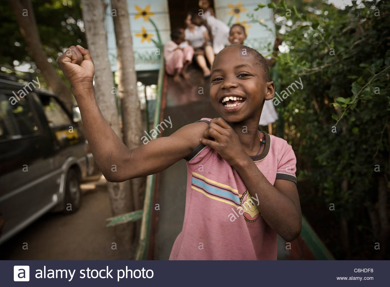 Young boy laughing and showing off his biceps - Stock Image