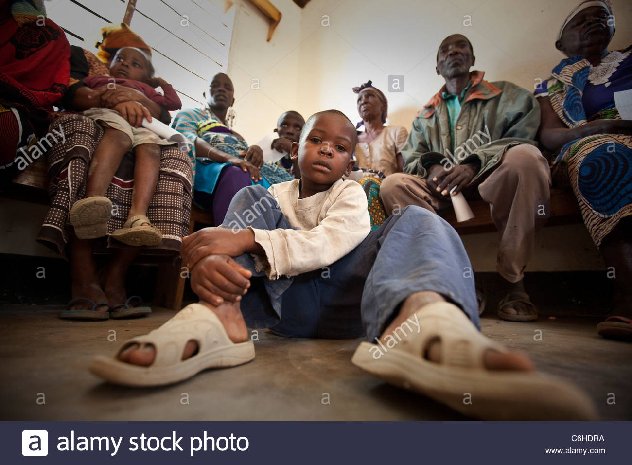 A young child waits to be seen by a doctor at a clinic - Stock Image