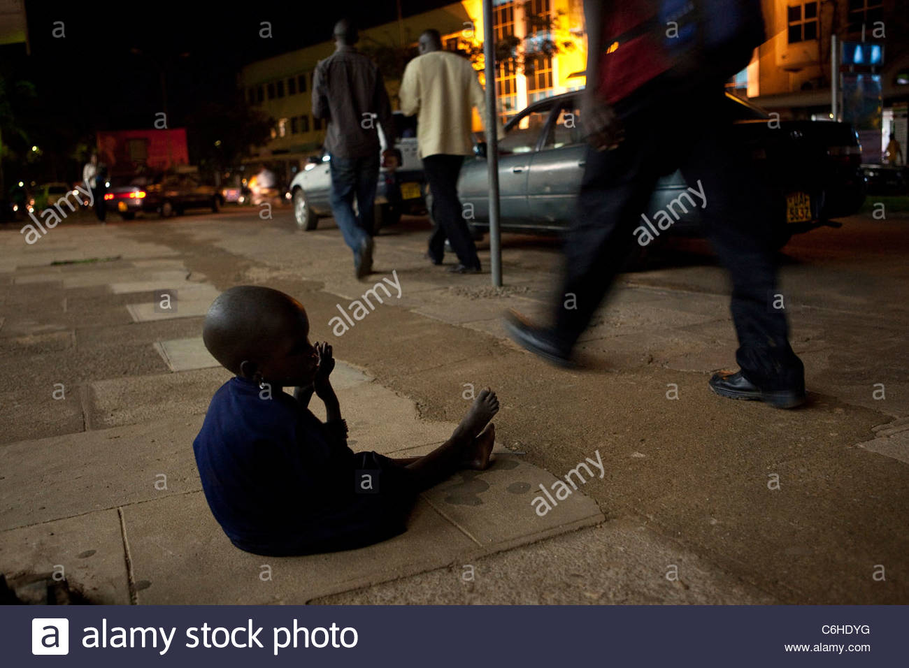 A young child begging on the pavement as pedestrians walk by - Stock Image