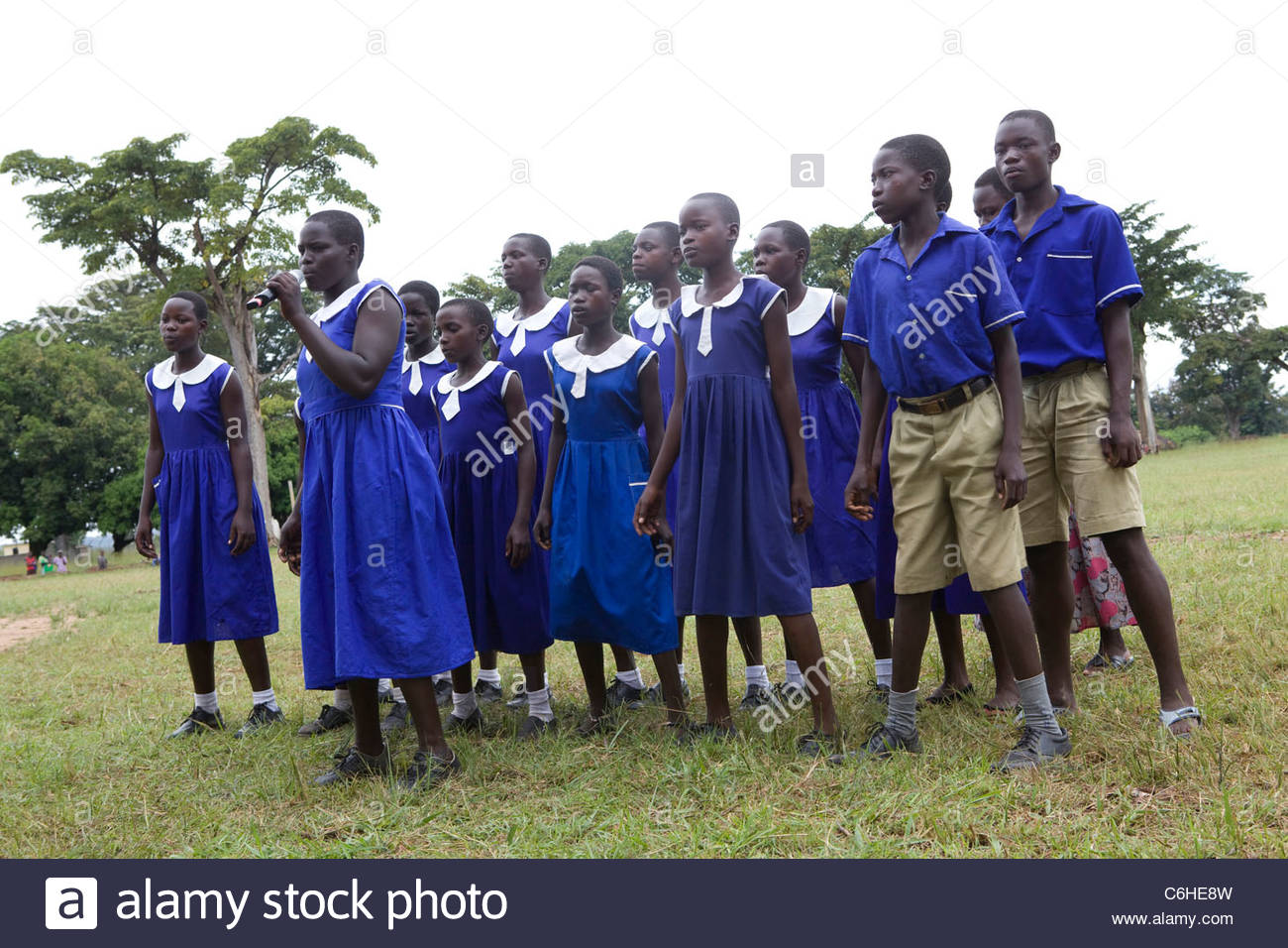 A group of school children sing outside their school. - Stock Image