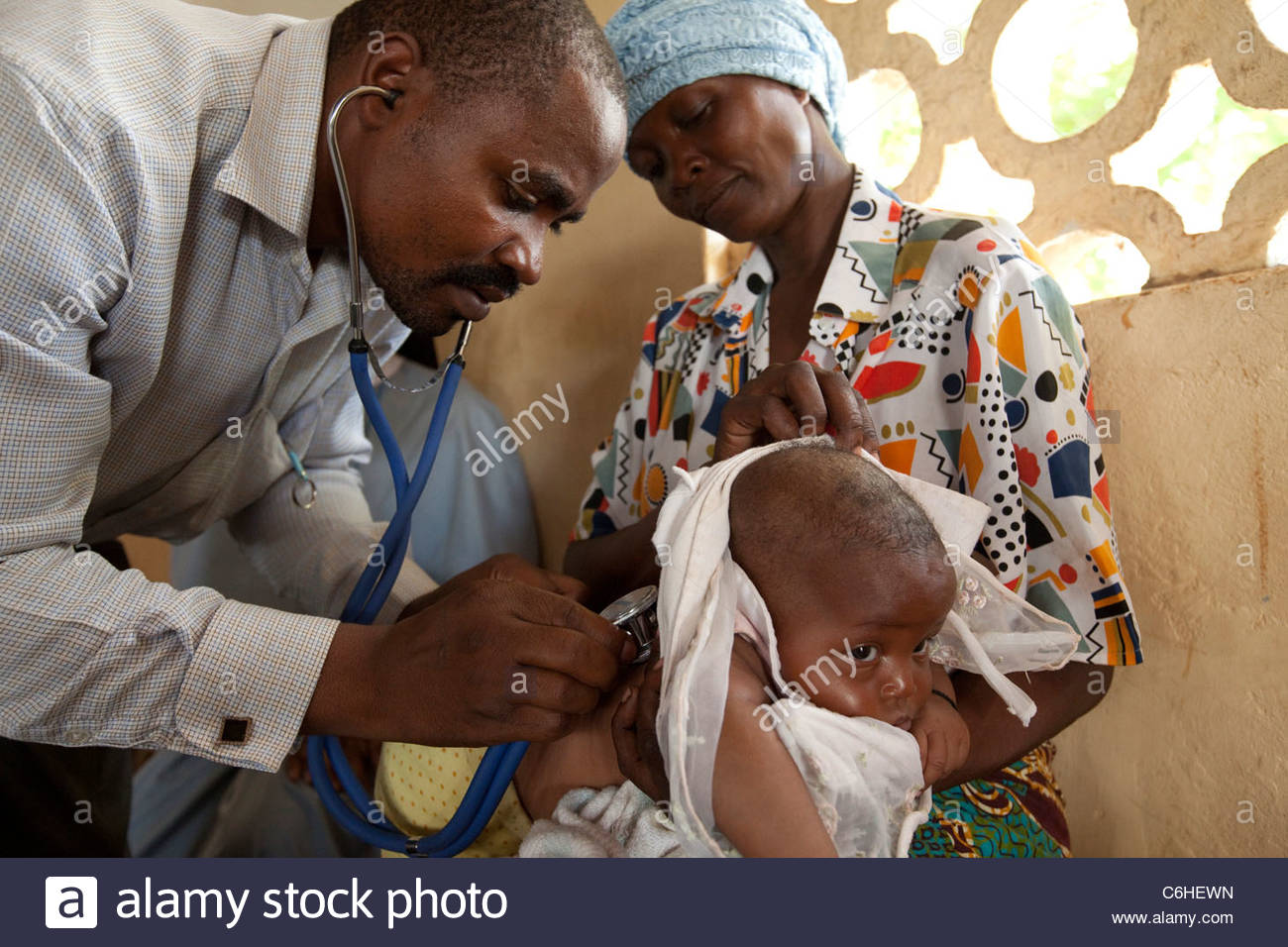 A doctor examines a small child at a medical dispensary - Stock Image