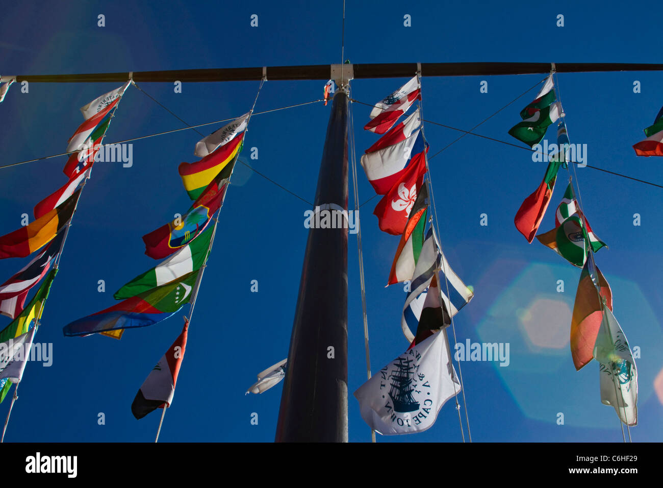 Flags on a tall flagpole in the V&A waterfront Stock Photo