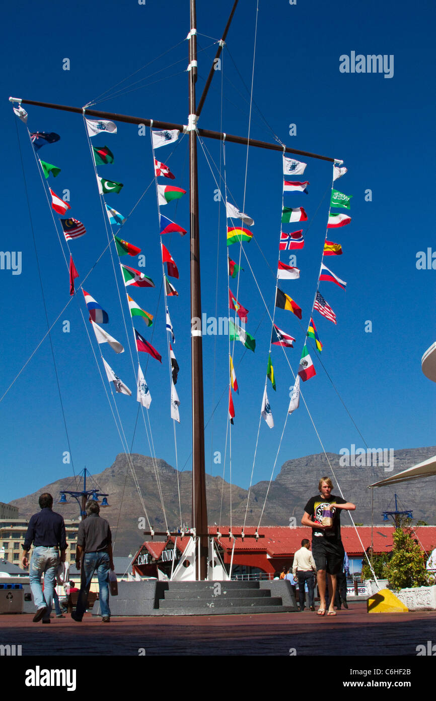 Flags on a tall flagpole in the V&A waterfront with Table Mountain in the background - Stock Image