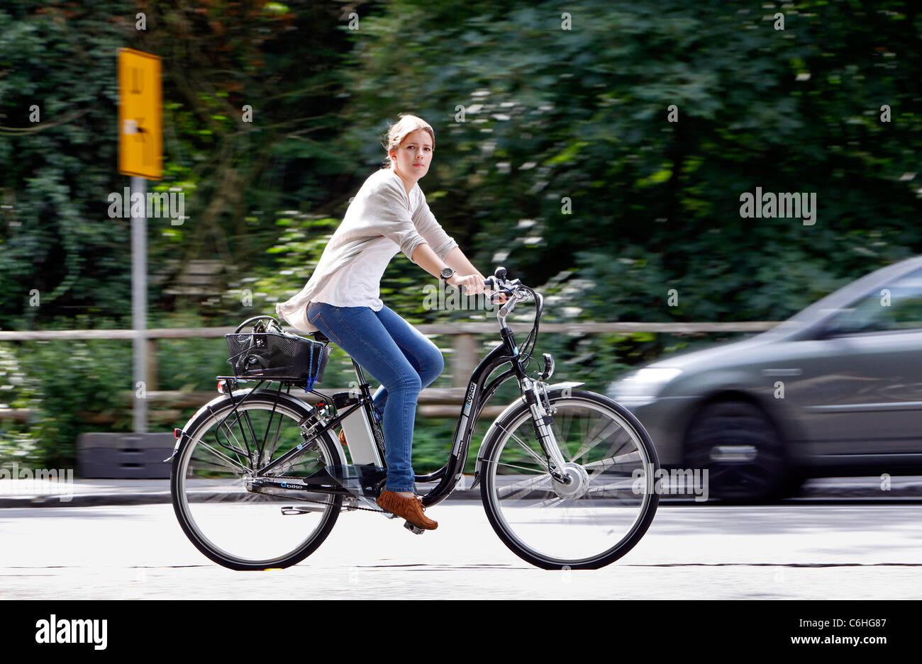 Girl riding on electric bicycle, pedelec, ebike, e-bike, Dortmund, Germany Stock Photo