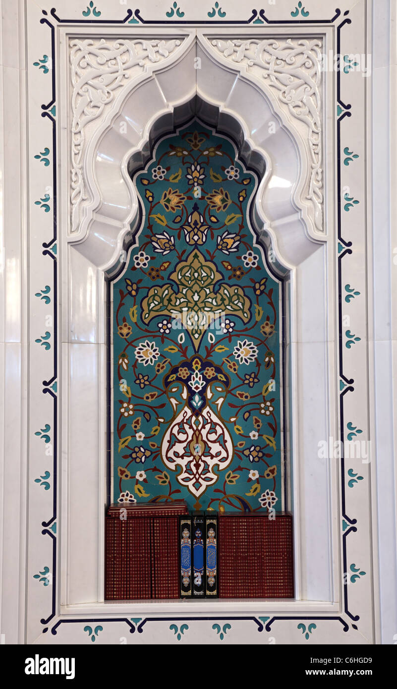 Oriental mosaic decoration in a mosque. Quran books in a shelf. Sultanate of Oman - Stock Image