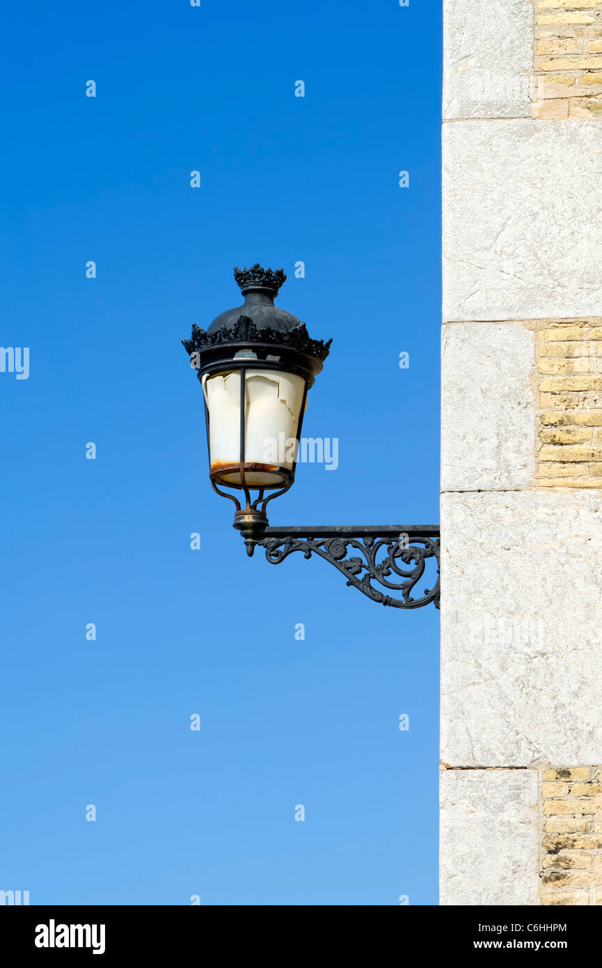 Old cast iron streetlight on a wall - Stock Image