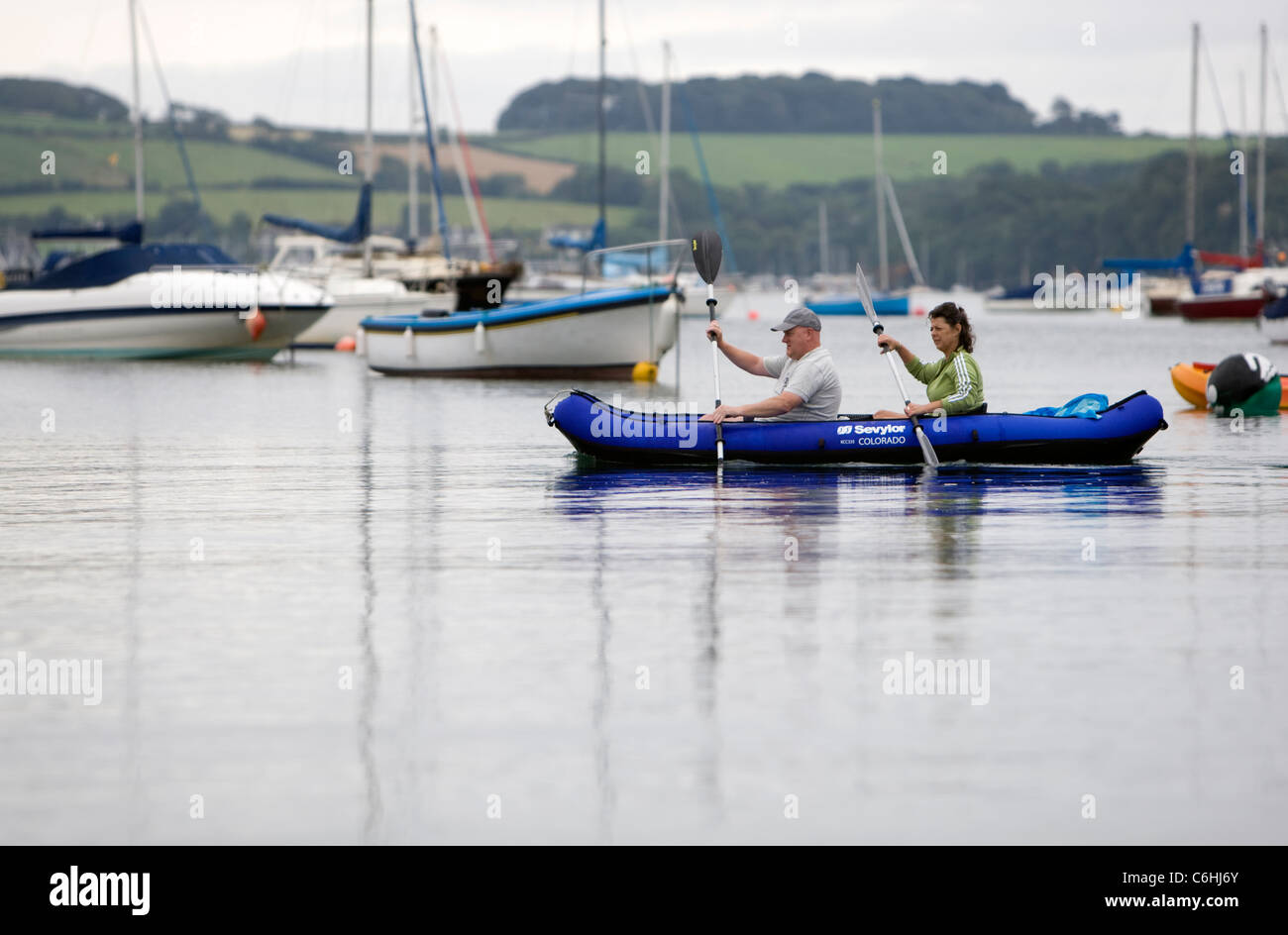 A couple paddle an inflatable kayak on calm sea at Loe Beach, Cornwall - Stock Image