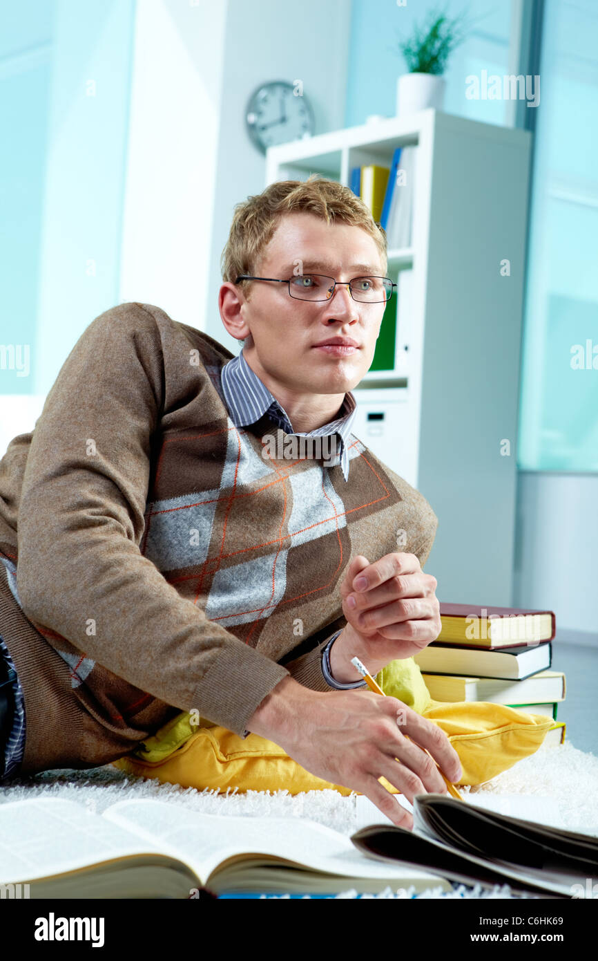Image of serious student lying on the floor and doing homework Stock Photo