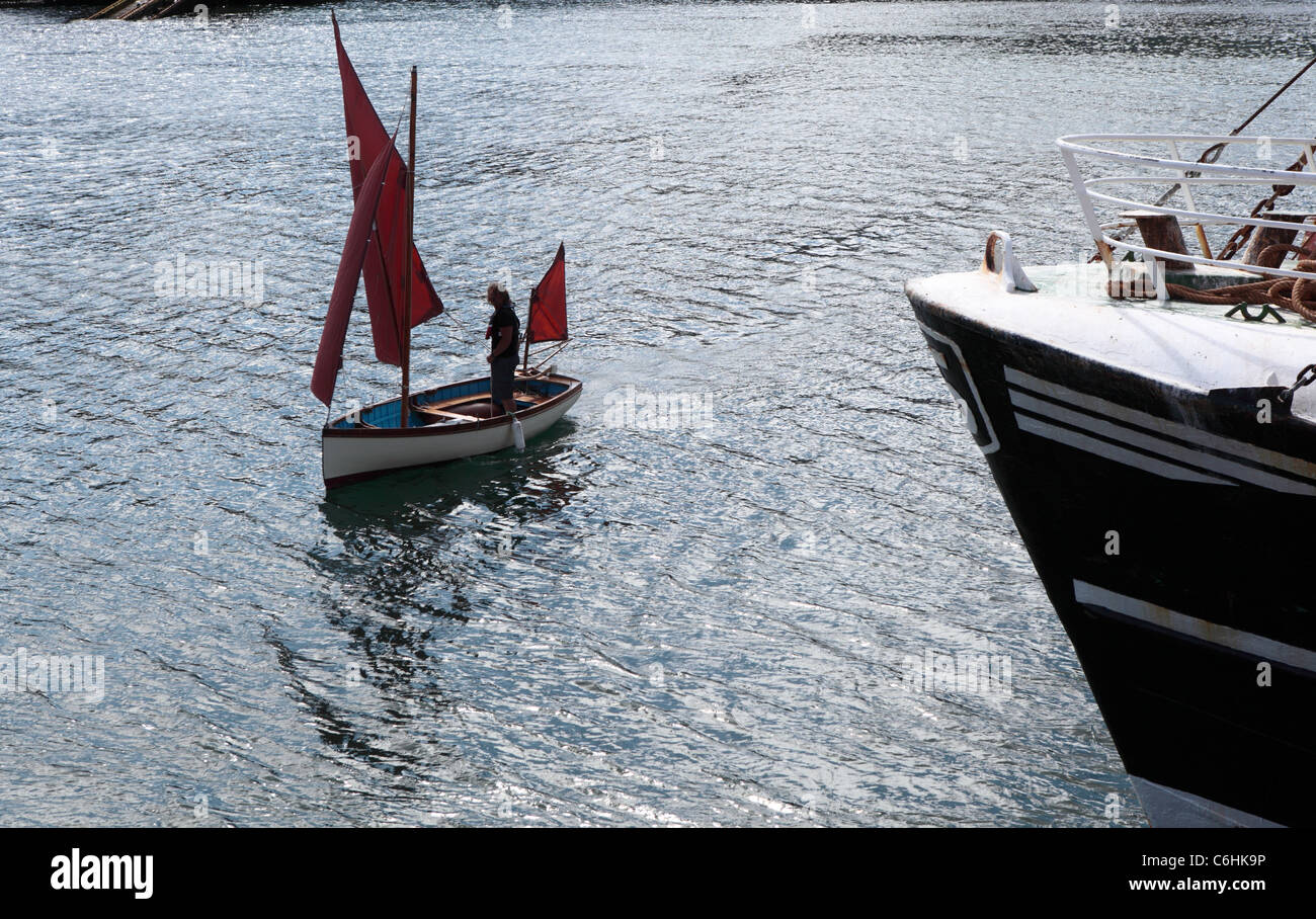 A small sailing boat with a red sail leaves the harbour at Newlyn, Cornwall - Stock Image