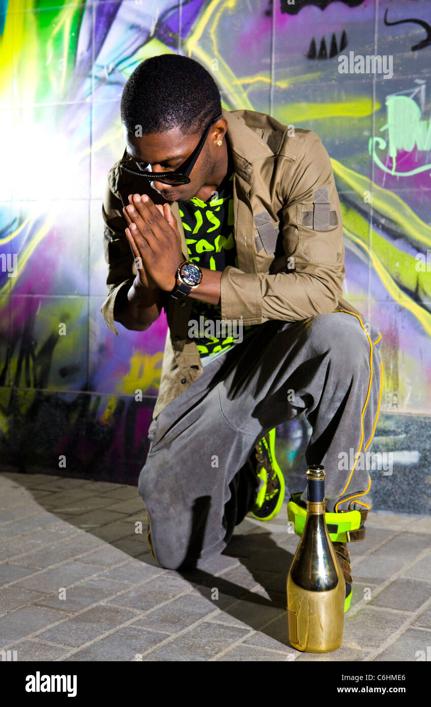 afro-american man offers prayers in front of colorful graffiti wall - Stock Image