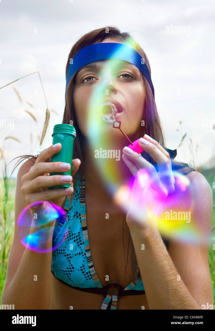 wistful young woman blowing soap bubbles at summer - Stock Image