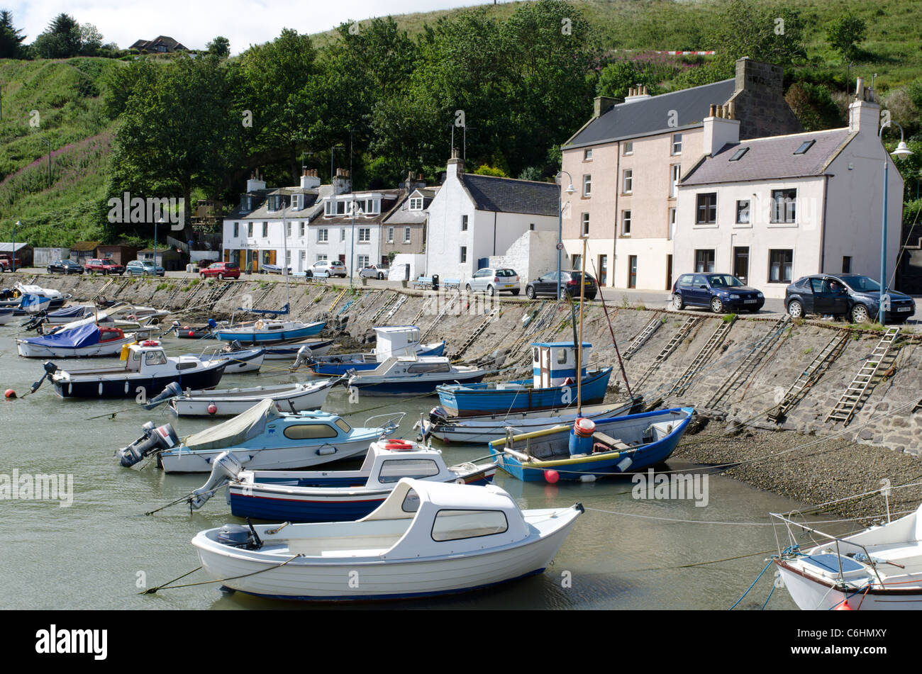 Leisure boats moored at shorefront with houses in Stonehaven Harbour - Kincardienshire - Stock Image