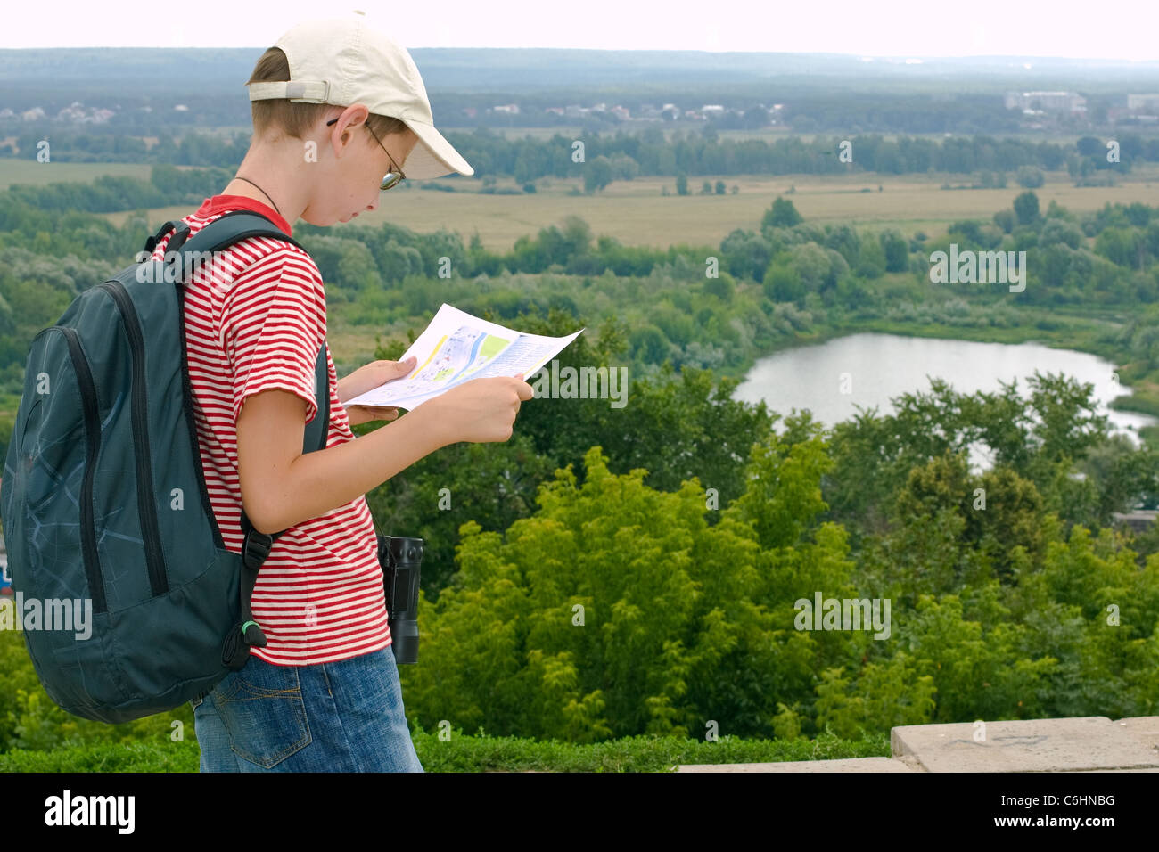 Boy with binoculars and backpack looks at the map on a hike - Stock Image
