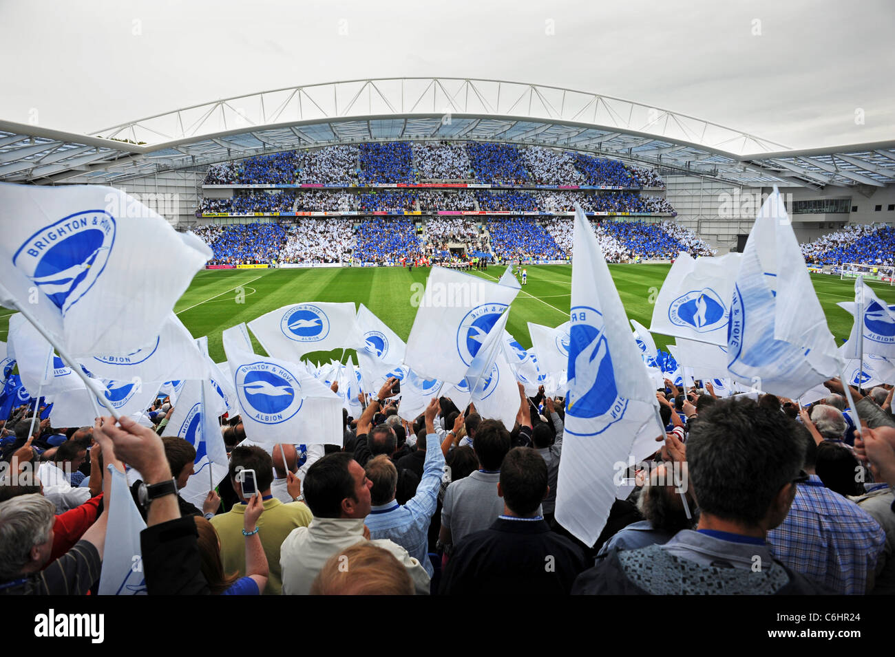 Brighton and Hove Albion football fans wave flags before the first Championship match ever to be played at the new - Stock Image