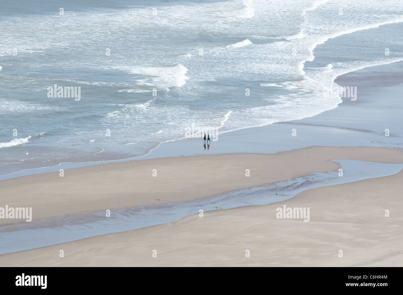 St Cyrus Beach National Nature Reserve with surf patterns and people walking - relaxing on sand 2 - Stock Image
