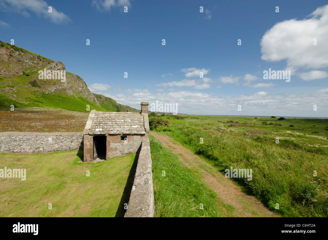 Stone hut in graveyard on bright sunny day at St Cyrus nature Reserve - Kincardineshire - Stock Image